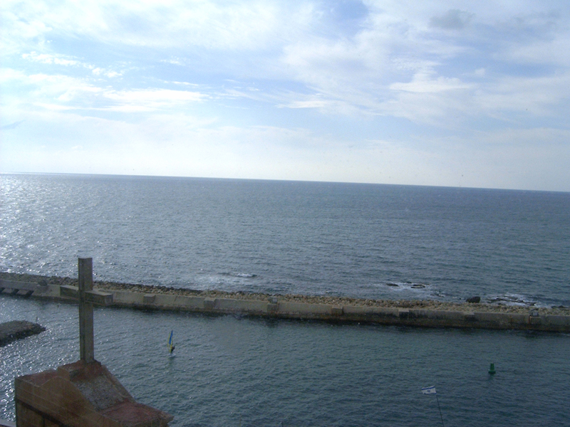 [The Mediterranean Ocean from the shore of Jaffa, Israel – with cross from steeple in foreground]